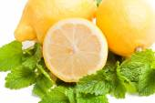 Halved lemon with two fruits on green lemon balm leaf — Stock Photo