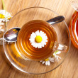 Herbal chamomile tea with fresh blossom in teacup, on wooden background — Stock Photo #76643027