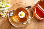 Herbal chamomile tea with fresh blossom in teacup, on wooden background — Stock Photo