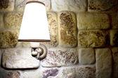Lampada splendente su un muro fatto di pietre — Foto Stock