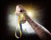 Hand with medal over stormy sky — Stock Photo