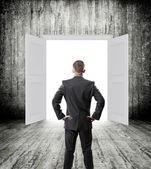 Businessman posing over doorway — Stock Photo