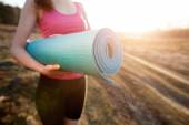 Woman walking with a yoga mat — Stock Photo