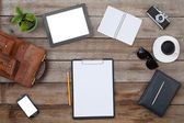 Blank paper on wood table with ipad style tablet pc and a smartphone — Stock Photo