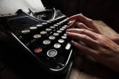 Hands writing on old typewriter over wooden table background — Stock Photo