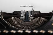 Business plan written by a typewriter on a paper sheet. Space fo — Stock Photo
