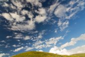 Green hill on blue sky with light clouds — Stock Photo