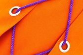 Orange fabric with ring and blue cords to tighten up — Stock Photo