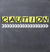 Caution text on blackboard — Stock Photo