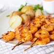 Grilled shrimp on skewer with potatoes and sauce — Stock Photo #52688861