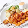 Grilled shrimp on skewer with potatoes and sauce — Stock Photo #52688875