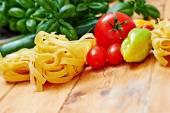 Raw tagliatelle with vegetables on  wooden table — Stock Photo