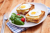 Croque madame with salad on wooden table — Stock Photo