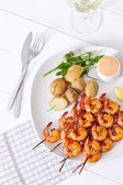 Grilled shrimp on skewer with potatoes and sauce — Stock Photo