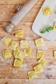 Raw ravioli pasta on wooden table — Stock Photo