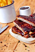 Barbecue ribs with fries on table — Stock Photo