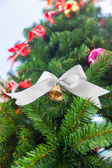 Small bell with white ribbon ornament on Christmas Tree — Stockfoto