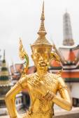 Golden Kinnara statue with flower in hand — Stock Photo
