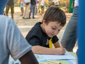 Young boy drawing on a paper with colored pencil in a park — Stock fotografie
