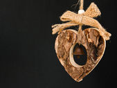 Bark wooden heart on a rope with little opaque brass bell in the — Stock Photo