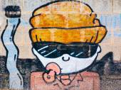 Boy with sunglasses graffiti,pacifier and orange hat near a big — Stock Photo