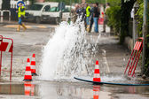 Road spurt water beside traffic cones — Stock Photo