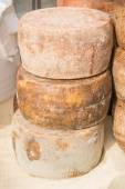 Stacked rounded cheese for sale in market — Stock Photo