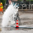 Road spurt water beside traffic cones and a technician in backgr — Stock Photo #60535223