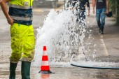Road spurt water beside traffic cones and a technician — Stock Photo