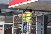 Worker on a scaffold under roofing — Stock Photo