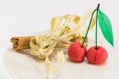 Sweet marzipan cherry fruit with cinnamon spicy stick decoration — Stock Photo