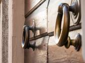 Brassy doorknob on wooden door, two handles — Stock Photo