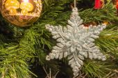 Bright silver six point star decoration on christmas tree — Stock Photo
