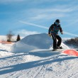 Freestyle snowboarder with helmet in snowpark — Stock Photo #67584239