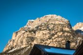 Mountain peak with shadow, sun and sky — Stock Photo