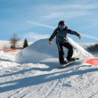 Freestyle snowboarder with helmet in snowpark — Stock Photo #68905889
