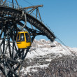 Yellow cable car ski lift going up on the mountain top — Stock Photo #70565647