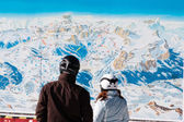 Skiers with safety helmets in front of ski map — Stock Photo