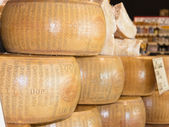 Round forms of Parmigiano Reggiano Italian cheese for sale — Stock Photo