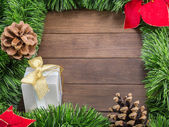 Christmas decoration with white gift, pine cones and poinsettia — Stock Photo