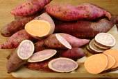 Raw sweet potatoes on wooden background  — Stock Photo