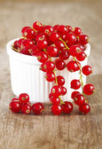 Redcurrants in bowl on wooden table — Stock Photo