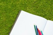 Color pencil and sketchbook on fresh spring green grass — Stock Photo