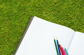 Color pencil and sketchbook on fresh spring green grass — Foto de Stock
