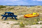Orange and yellow kayak on a sandy dune by the sea — Stockfoto