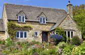 Old traditional English honey golden brown stoned cottage with colourfu flowering front garden on a summer sunny day — Stock Photo