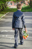 Boy with a bouquet of flowers waiting for a girl on a date — Stock Photo