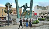 People observe attentively a statue of hercules in the city — Stock Photo