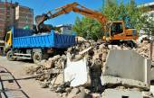 A backhoe and a truck perform their work in the work of a great city. — Stock Photo
