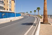 Road with palm trees next to the mediterranean sea — Stock Photo